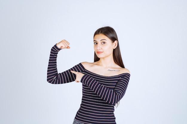 Giovane donna in camicia a righe che mostra il suo muscolo del braccio e il pugno