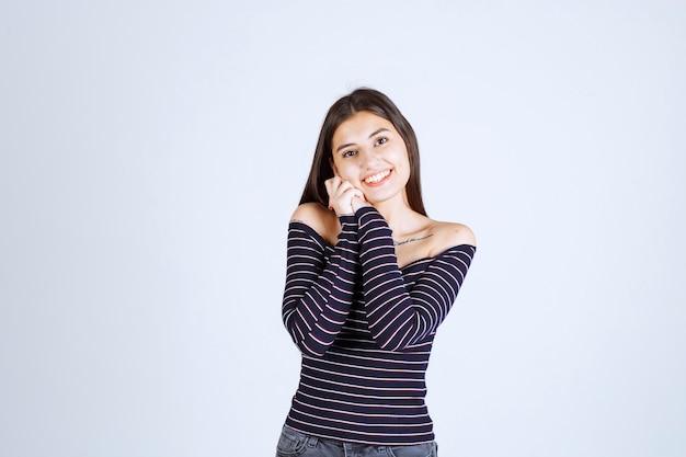 Giovane donna in camicia a righe che unisce le mani e che dà pose incantevoli