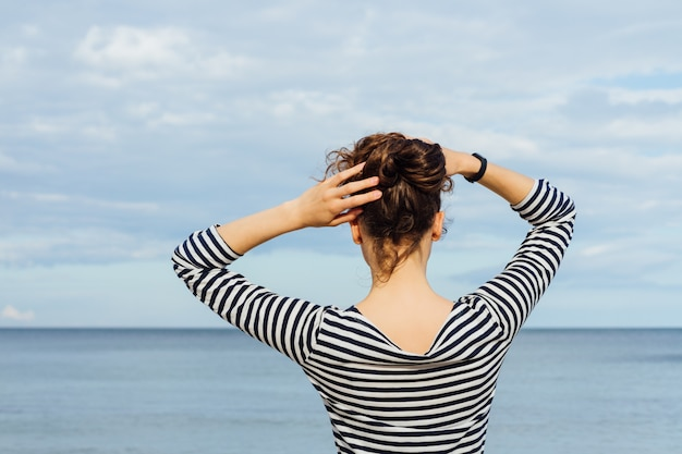 Young woman in striped t-shirt and with curly hair looking at the sea and holds her hair