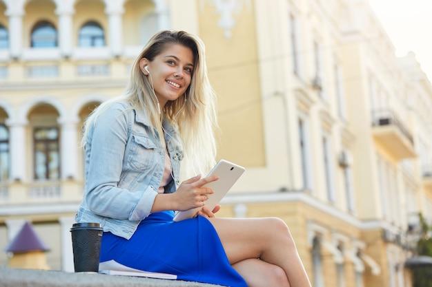 講義後座っている若い女性学生、コーヒーを飲む、ヘッドフォンの音楽で聴く、白いタブレットで何かを読む