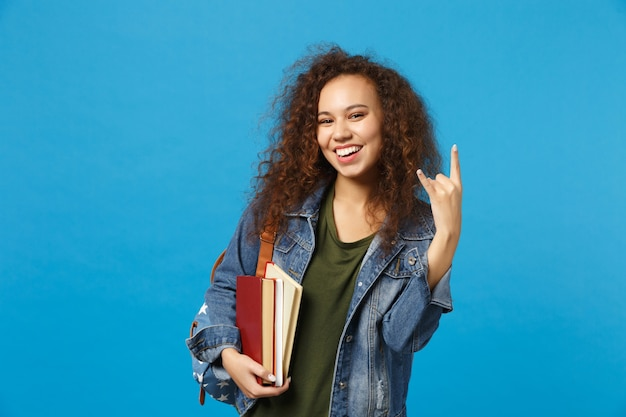 Young woman student in denim clothes and backpack holds books isolated on blue wall