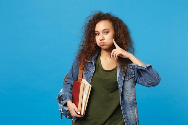 La giovane studentessa in vestiti del denim e lo zaino tiene i libri isolati sulla parete blu