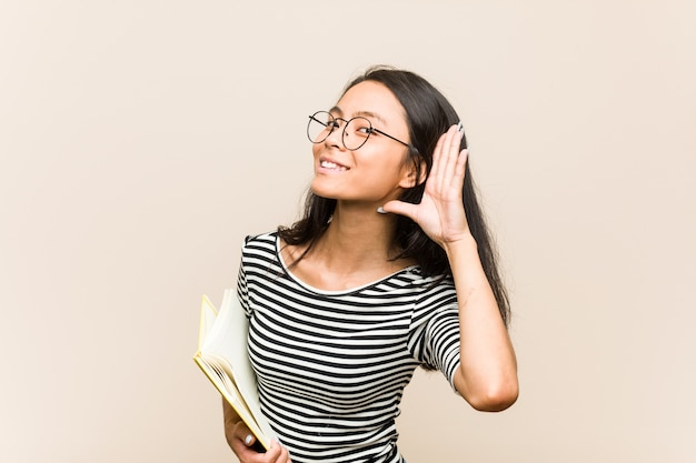 Young woman student holding a book