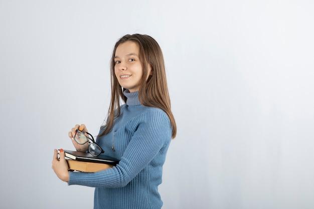 책과 안경을 들고 젊은 여자 학생.