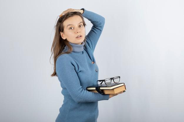 Giovane studentessa in possesso di libri e bicchieri.