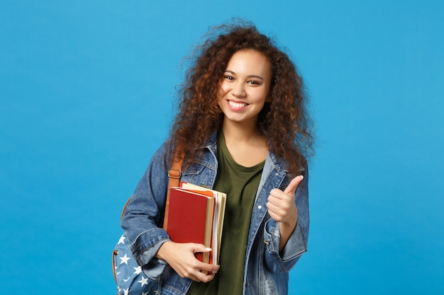 デニムの服とバックパックの若い女性の学生は青い壁に隔離された本を保持します。