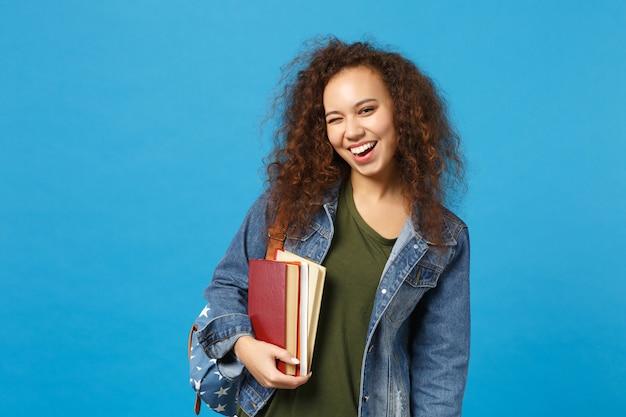 デニムの服とバックパックの若い女性の学生は青い壁に隔離された本を保持します。 無料写真