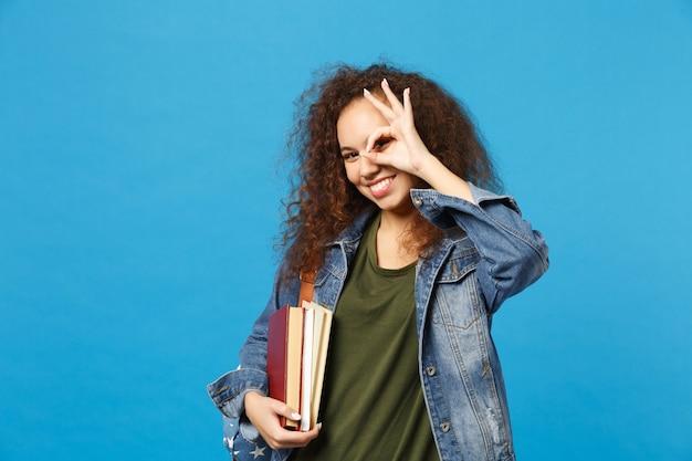 Молодая женщина-студент в джинсовой одежде и рюкзаке держит книги, изолированные на синей стене
