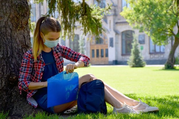 防護マスクの若い女性学生は大学近くの木の下の芝生の上に座っています。検疫後、学校に戻ります。新しい正常。
