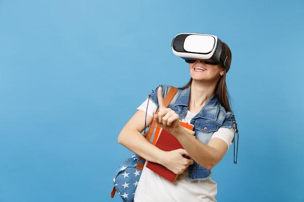 Студент молодой женщины в виртуальной реальности glassess держать книги касаются чего-то вроде кнопки, указывая на плавающий виртуальный экран, изолированный на синем фоне. обучение в школе университетского колледжа.