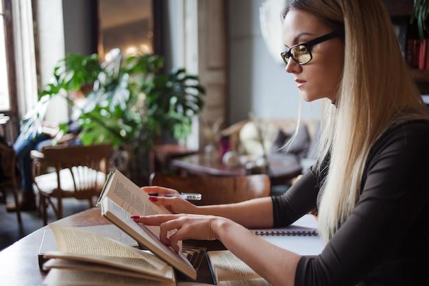 Молодая женщина студентка университета. подготовка к экзамену и изучение уроков в публичной библиотеке. сидя за столом в окружении большого количества учебников
