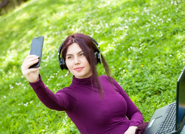 Young woman student in the park listening music with headphones take a selfie.