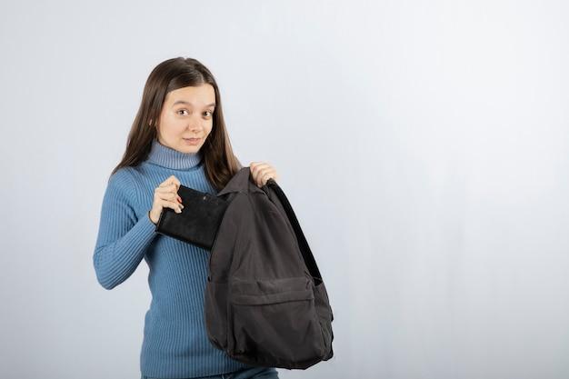 Giovane studentessa che mette il taccuino nello zaino.