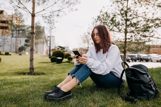 スマートフォンを見て公園の芝生に座っている若い女性学生