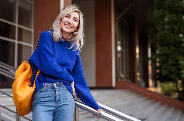 大学の階段で笑っている若い女性学生