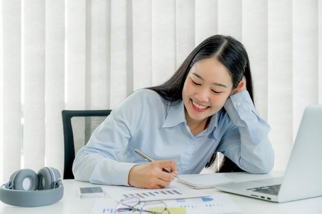 自宅からノートパソコンの勉強オンラインクラスのビデオ会議教育eラーニングコースを見てメモを取る若い女性の学生。
