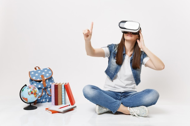 Young woman student in virtual reality glasses touch something like push on button, pointing at floating virtual screen near globe backpack school book isolated on white wall