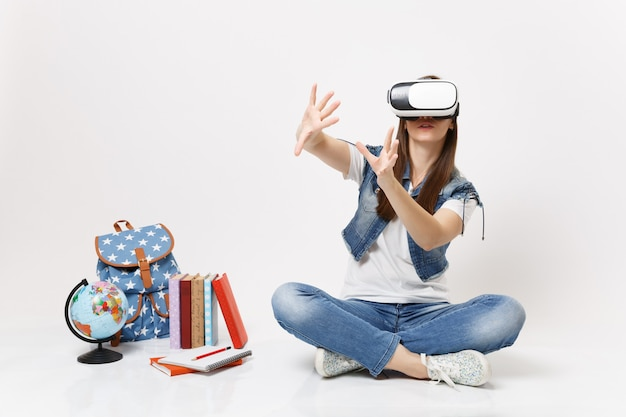 Young woman student in virtual reality glasses touch something like push on button, pointing at floating virtual screen near globe backpack school book isolated