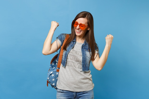 Young woman student with closed eyes with backpack in orange heart glasses clenching fists like winner or happy human isolated on blue background. education in college. copy space for advertisement.