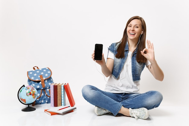 Young woman student with earphones mobile phone with blank black empty screen listen music show ok sign near globe, backpack books isolated