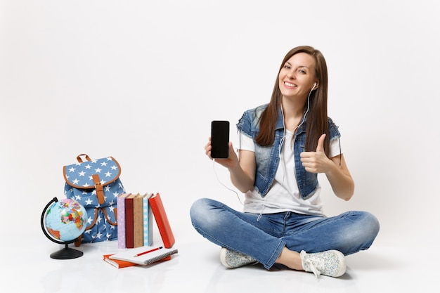 Young woman student with earphones mobile phone with blank black empty screen listen music show thumb up near globe backpack books isolated