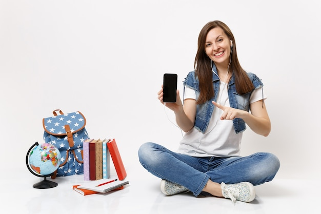 Young woman student with earphones pointing finger on mobile phone with blank empty screen listen music near globe, backpack books isolated