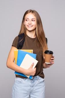 Студент молодой женщины с телефоном, изолированные на белой стене