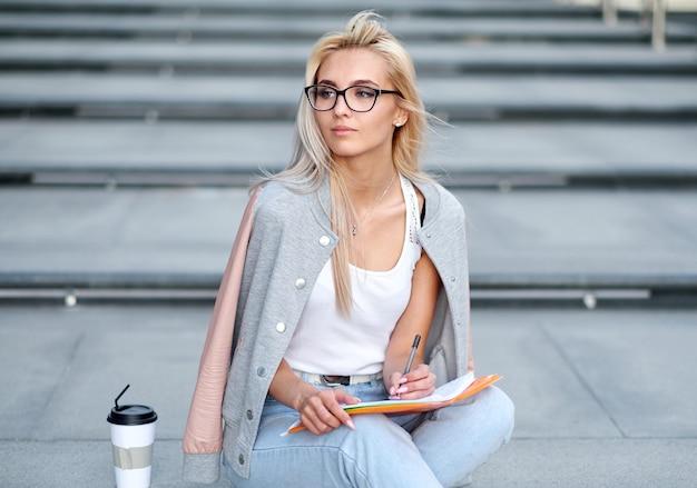 폴더, 책, 커피와 함께 대학 계단에 캠퍼스에 젊은 여자 학생
