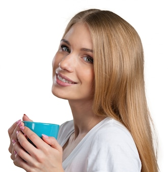 Young woman on studio background drinks coffee or tea