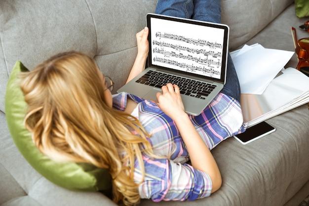 온라인 코스 또는 무료 정보를 혼자서 집에서 공부하는 젊은 여성. 뮤지션, 바이올리니스트가되어 격리 된 상태에서 코로나 바이러스 확산에 대한 격리. 노트북, 스마트 폰 사용.