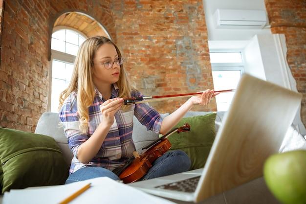 Молодая женщина учится дома во время онлайн-курсов или самостоятельно получает бесплатную информацию. становится музыкантом, скрипачом в изоляции, на карантине от распространения коронавируса. используя ноутбук, смартфон.