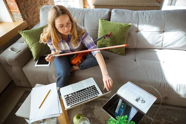オンラインコースや無料の情報を自分で自宅で勉強している若い女性。孤立している間はミュージシャン、バイオリニストになり、コロナウイルスの拡散を隔離します。ノートパソコン、スマートフォンを使用。