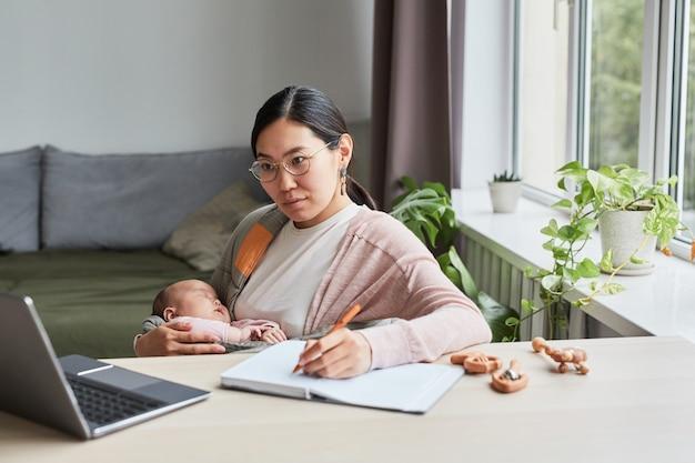 Молодая женщина учится дома, она сидит за столом, смотрит в ноутбук и делает заметки в записной книжке ...