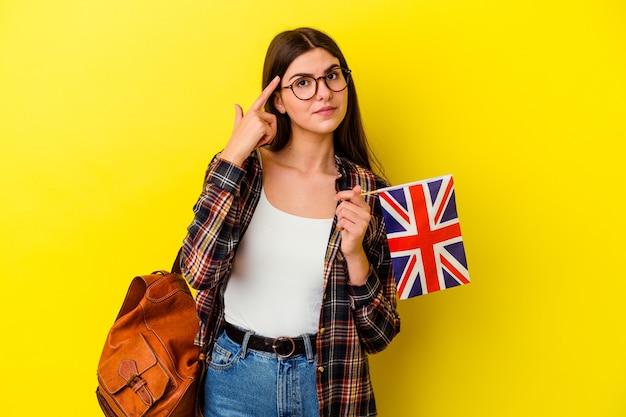 ピンクの壁に指で寺院を指して、考えて、タスクに焦点を当てて孤立した英語を勉強している若い女性。