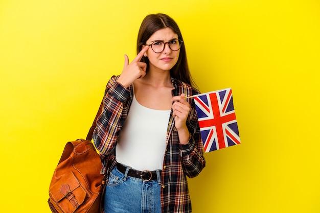 집게 손가락으로 실망 제스처를 보여주는 분홍색 벽에 고립 된 영어를 공부하는 젊은 여자