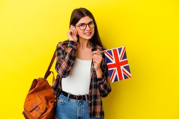 手で耳を覆うピンクで英語を勉強している若い女性。