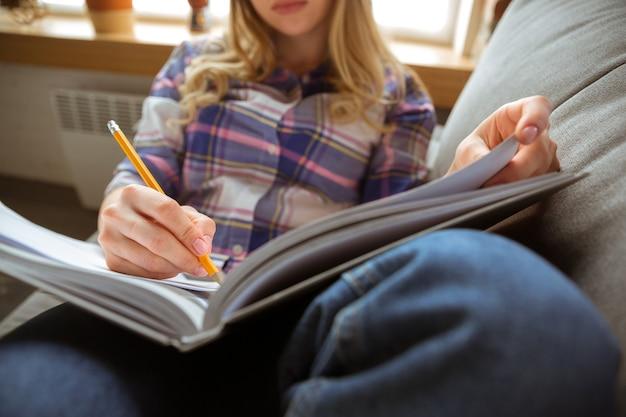 Giovane donna che studia a casa durante i corsi online o libera informazione da sola prendendo appunti