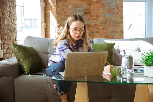 Giovane donna che studia a casa durante i corsi online o informazioni gratuite da sola