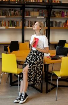 Giovane donna che studia in biblioteca