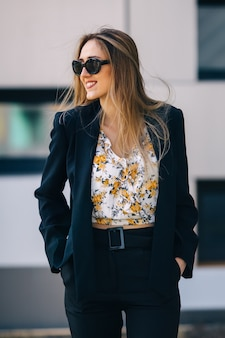 Young woman in a stylish black suit hold hands in her pockets