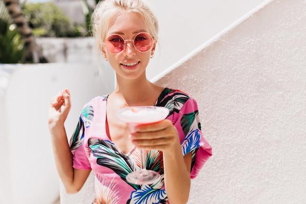 Giovane donna in vestiti alla moda, bere un cocktail in una giornata estiva.