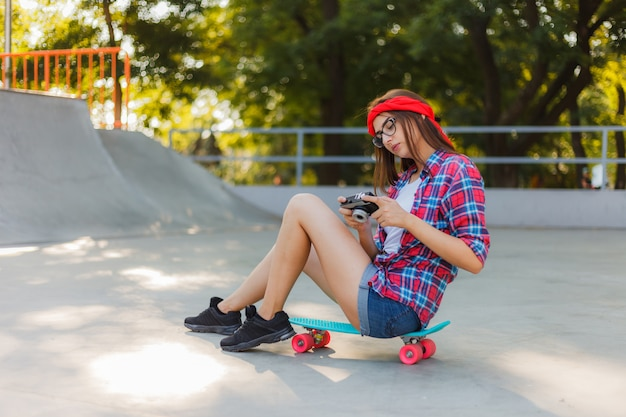 Young woman in stylish clothes sits on a skateboard and uses retro camera in skatepark on bright sunny day. youth concept