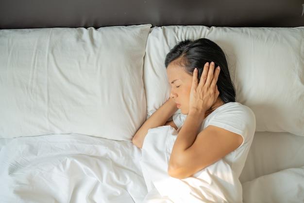 Молодая женщина страдает и обеспокоена шумными соседями и закрывает уши руками, пытаясь заснуть дома рано утром.