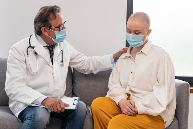 Young woman suffering of breast cancer talking with her doctor