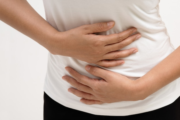 Young woman suffering from abdominal pain feeling stomach ache, symptom of pms