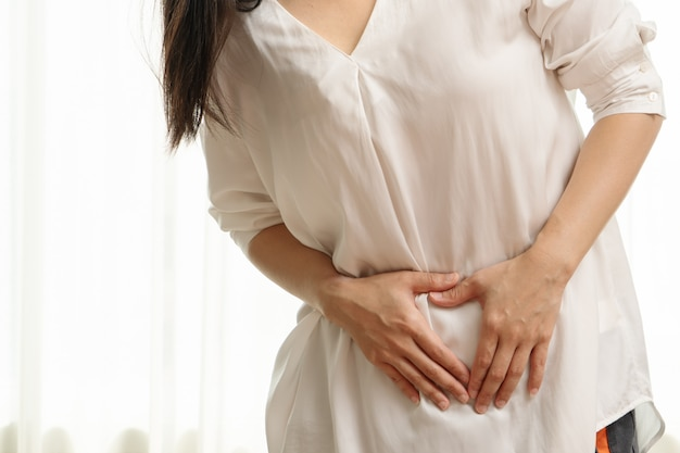 Young woman suffering from abdominal pain feeling stomachache, symptom of pms on white background