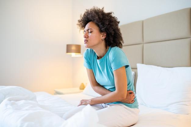 自宅のベッドに座っている間腹部の痛みに苦しんでいる若い女性。ベッドの上に座って、胃の痛みを持つ女性。
