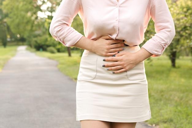 공원에서 산책하는 동안 복통으로 고통받는 젊은 여자.