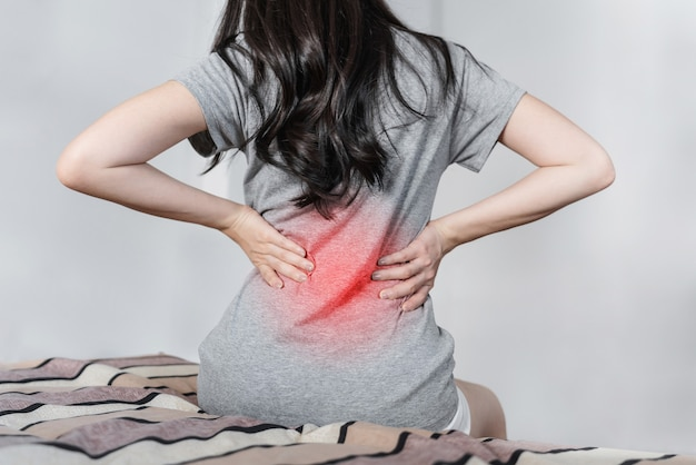 Young woman suffering from back pain on bed after waking up