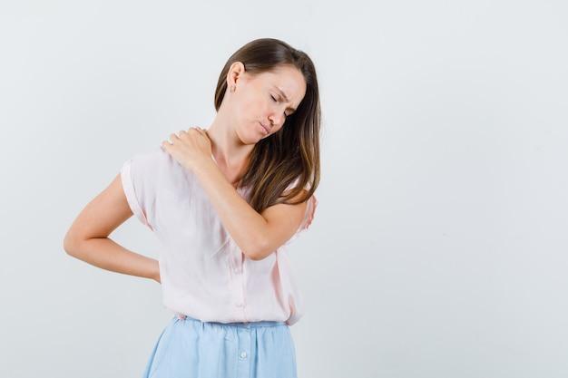 Молодая женщина страдает от боли в спине в футболке, юбке и выглядит усталой, вид спереди.